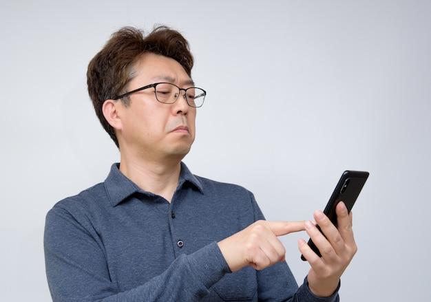 Aziatisch mannetje dat iets op zijn mobiele telefoon probeert te lezen. slecht zicht, presbyopie, bijziendheid.
