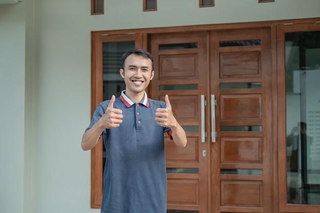 Aziatisch mannetje staat met duimen tegen nieuw huis