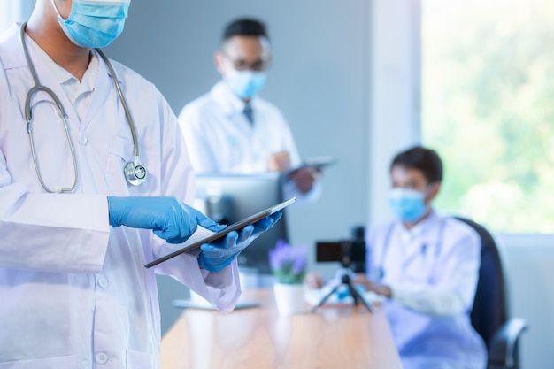 Aziatisch medisch team die het medische concept van de het netwerkteamvergadering van de maskerstechnologie dragen.