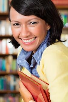 Aziatisch meisje bij bibliotheek die een boek houdt