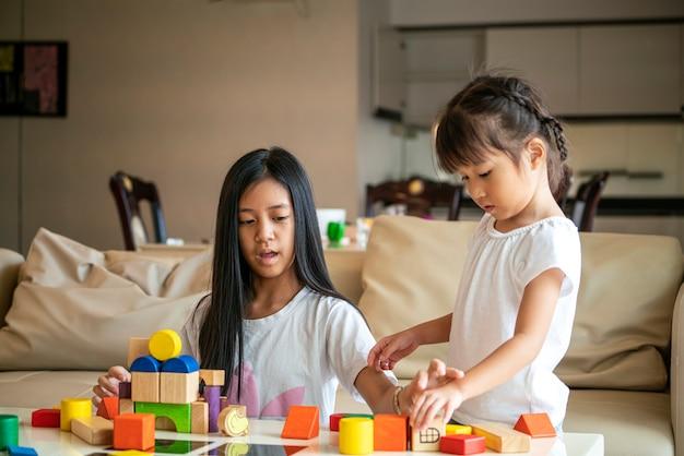 Aziatisch meisje brengt quality time samen door voor het spelen van houten blok speelgoed met haar zus in de woonkamer thuis. aziatische familie- en kinderconcepten