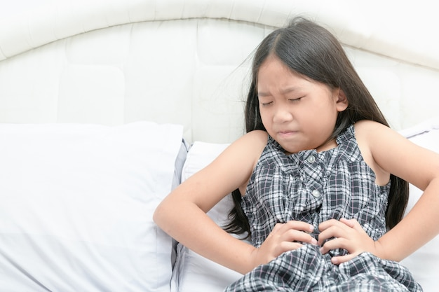 Aziatisch meisje dat aan maagpijn lijdt