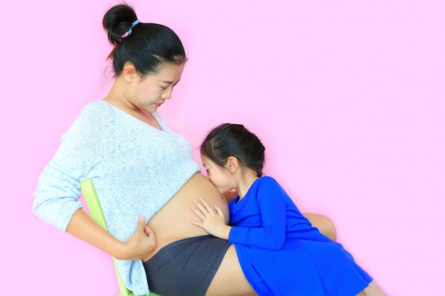 Aziatisch meisje dat de buik van de zwangere moeder kust