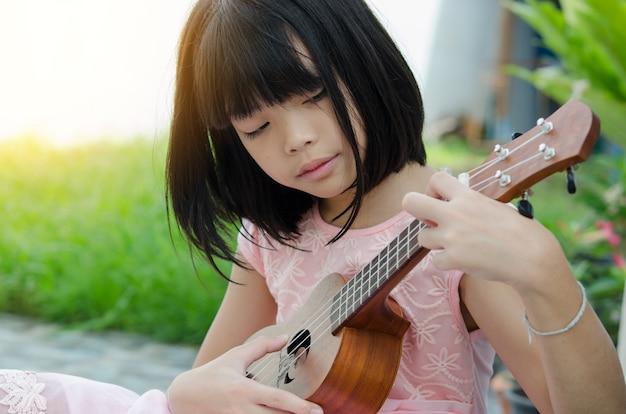 Aziatisch meisje dat de ukelele speelt