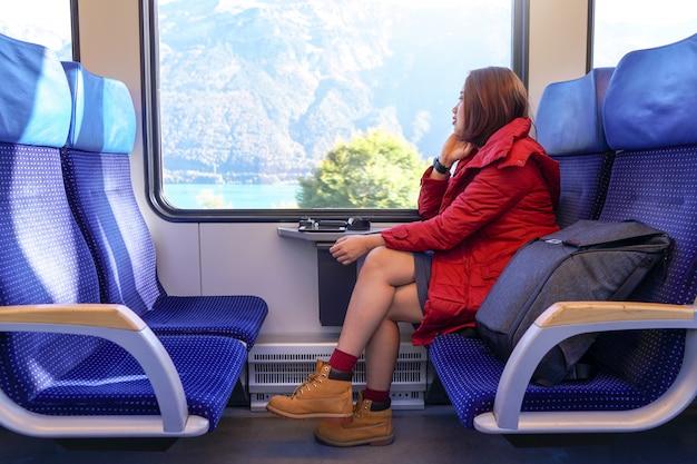 Aziatisch meisje dat door trein reist en uit aan het venster met rugzak kijkt.
