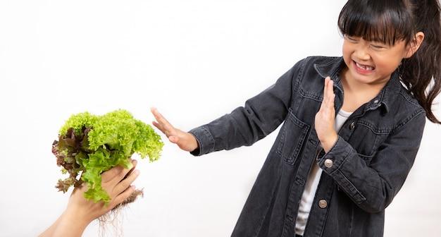 Aziatisch meisje dat een groene salade houdt die hij niet van houdt