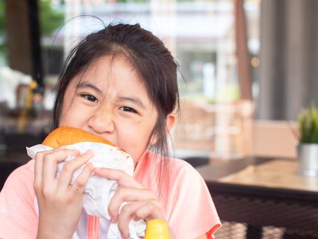 Aziatisch meisje dat een hamburger eet. aziatische kinderen eten kip kaas hamburger.