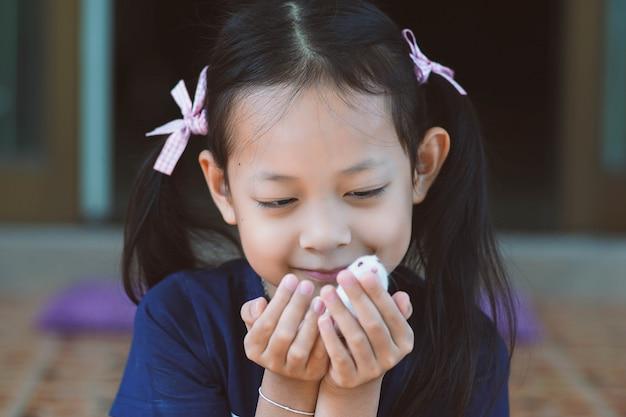 Aziatisch meisje dat een huisdierenrat met liefde houdt en gelukkig