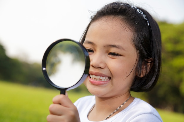 Aziatisch meisje dat een vergrootglas in openlucht houdt