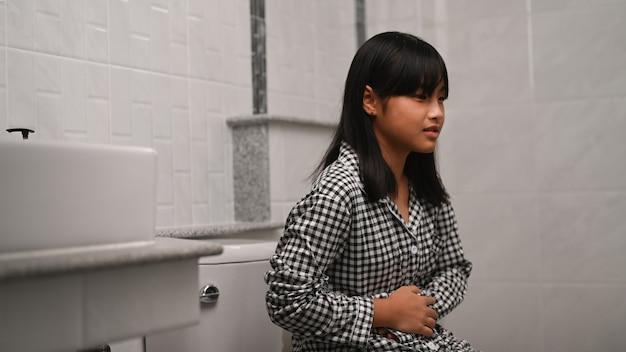 Aziatisch meisje dat haar buik vasthoudt en buikpijn heeft terwijl ze thuis op het toilet zit.