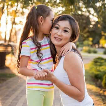 Aziatisch meisje dat haar moeder kust
