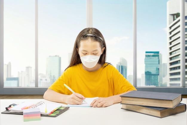 Aziatisch meisje dat het masker draagt en haar huiswerk thuis doet. online onderwijs tijdens quarantaine