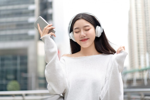Aziatisch meisje dat hoofdtelefoons draagt en aan streaming muziek met gesloten ogen luistert