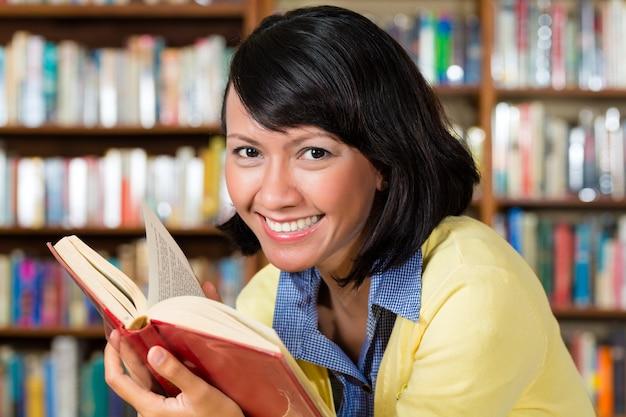 Aziatisch meisje dat in bibliotheek een boek leest