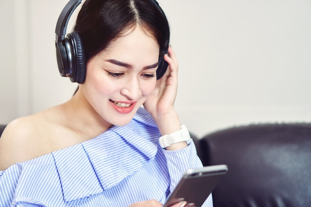 Aziatisch meisje dat in blauwe toevallige kleding aan muziek van zwarte hoofdtelefoons luistert.