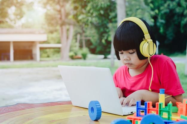 Aziatisch meisje dat laptop en hoofdtelefoons met behulp van