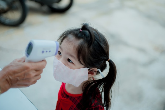Aziatisch meisje dat lichaamstemperatuur meet en een gezichtsmasker draagt.