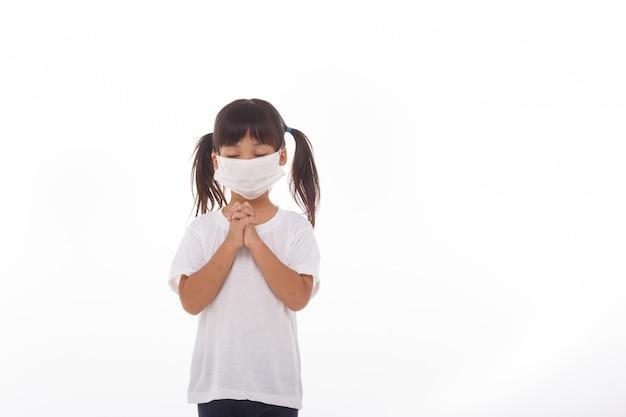 Aziatisch meisje dat masker het bidden draagt