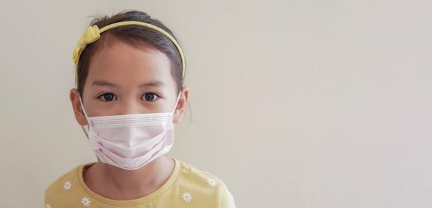 Aziatisch meisje dat medisch gezichtsmasker draagt om coronavirus, luchtverontreiniging en gezondheidsconcept te beschermen