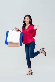 Aziatisch meisje dat met het winkelen zakken opgewekt over verkoopbevordering voelt