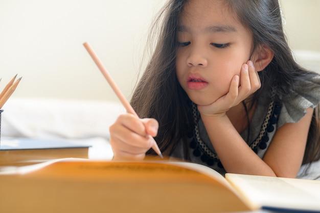 Aziatisch meisje dat met potlood en notitieboekje schrijft