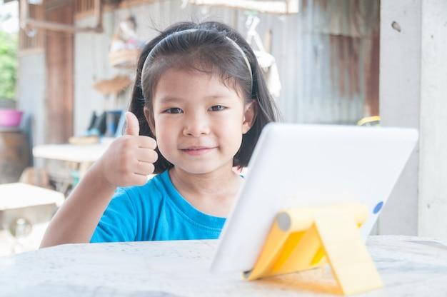 Aziatisch meisje dat online cursus leert of thuis spel online speelt.