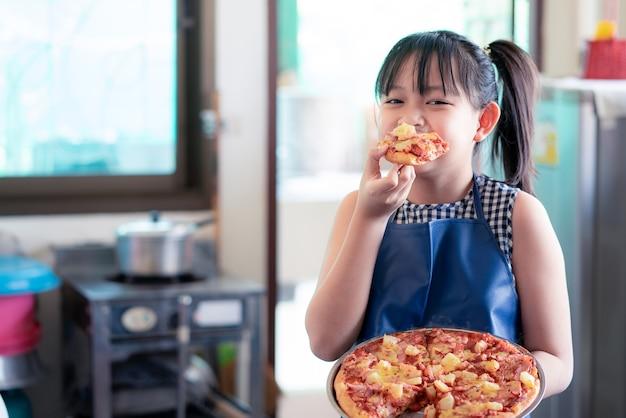 Aziatisch meisje dat pizza eet met heerlijk en geluk na het maken van zelfgemaakte pizza in de thuiskeuken
