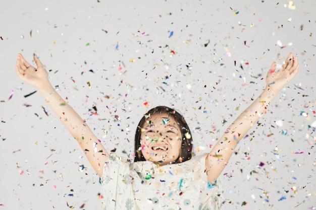 Aziatisch meisje dat pret met kleurrijke confettien op grijs heeft.