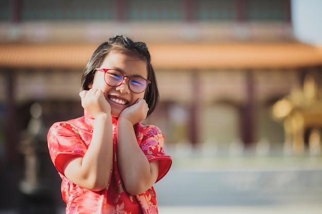 Aziatisch meisje dat rood chinees kostuumgeluk draagt tegen de tempelachtergrond van china