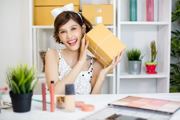 Aziatisch meisje dat thuis bureau en sorterende pakketpostdoos aan leveringsdienst aan klant werkt