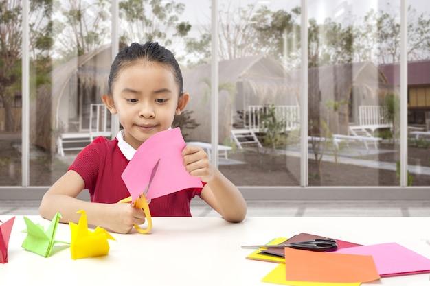 Aziatisch meisje dat thuis een papier snijdt