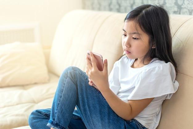 Aziatisch meisje dat thuis mobiele telefoon in haar handen bekijkt. ruimte voor tekst kopiëren