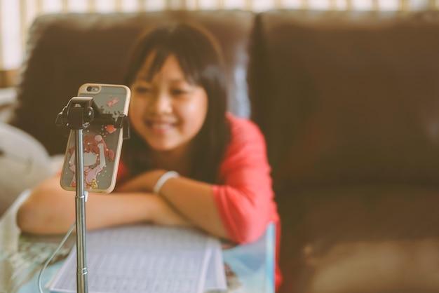 Aziatisch meisje dat thuis online studeert, glimlachend en gelukkig naar het telefoonscherm kijkt
