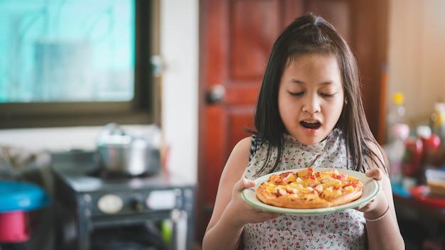 Aziatisch meisje dat zelfgemaakte pizza bereidt in de huiskeuken met verrassing