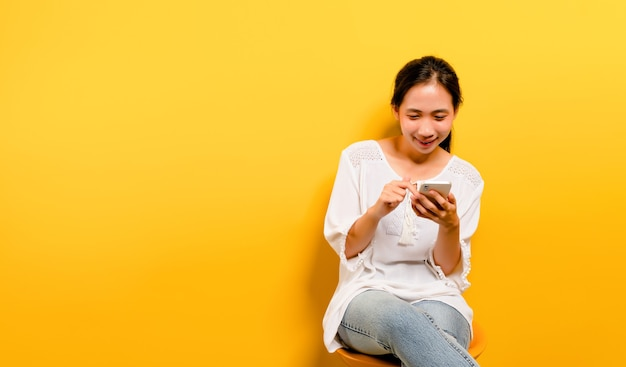 Aziatisch meisje dat zich gelukkig voelt en zit en typt op een smartphone op een gele achtergrond leuke aziatische g