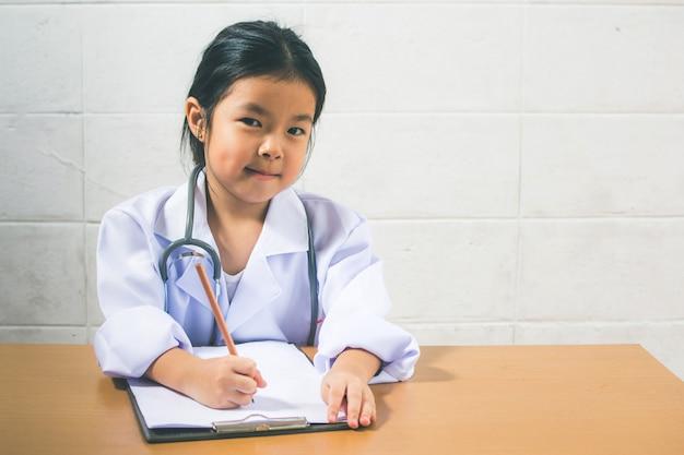 Aziatisch meisje die als arts het schrijven voorschrift en het voorbereiden van patiëntenrapport dragen