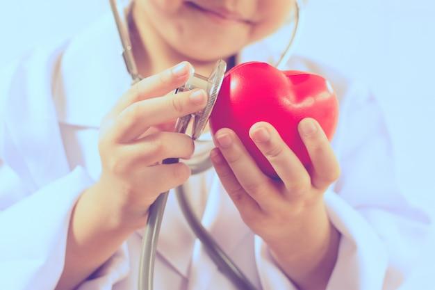 Aziatisch meisje die als artsenzorg gezond hart spelen