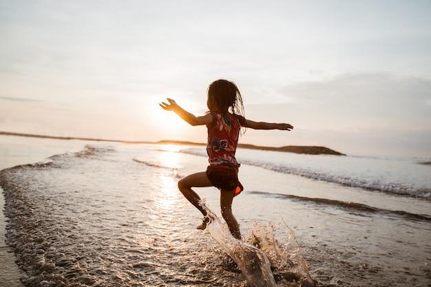 Aziatisch meisje die en op het strand lopen springen