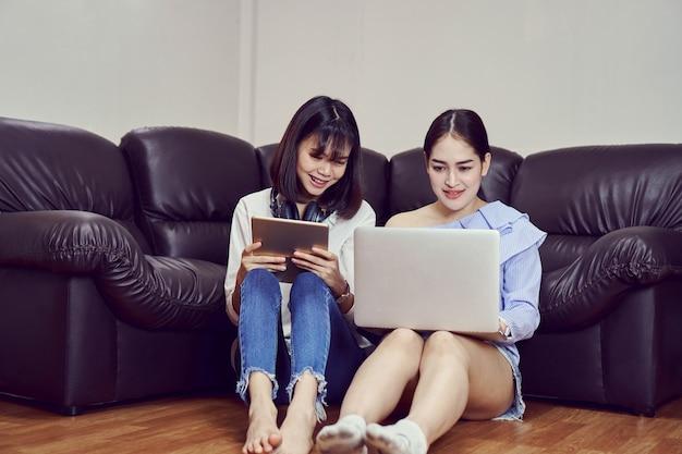 Aziatisch meisje die in blauwe toevallige kleding aan muziek van zwarte hoofdtelefoons luisteren en laptop gebruiken.