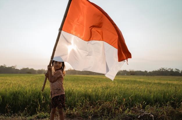 Aziatisch meisje die indonesische vlag klappen