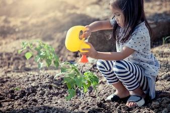 Aziatisch meisje die jonge boom met het water geven van pot in uitstekende kleurentoon water geven
