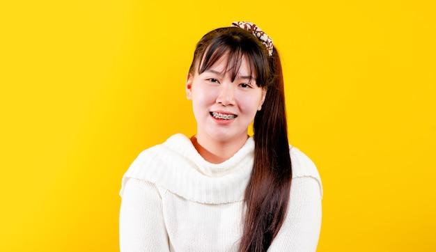 Aziatisch meisje die vrolijke, leuke, stralende glimlach. uitdrukking van liefdevolle ogen goed leven en geluk op het werk, ontspanning, tegen een gele achtergrond