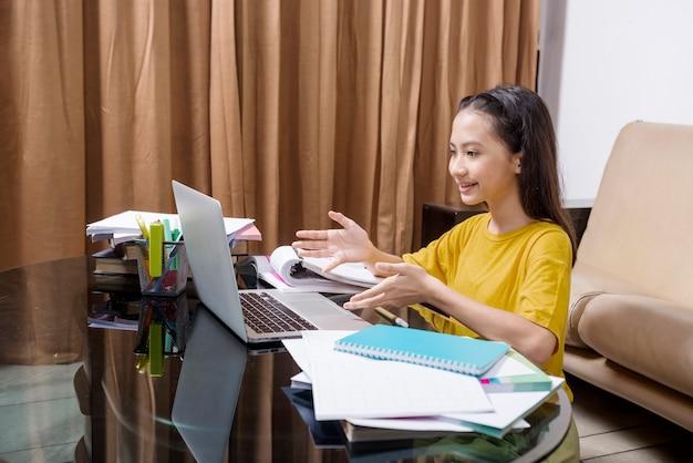 Aziatisch meisje doet haar huiswerk met laptop thuis. online onderwijs tijdens quarantaine