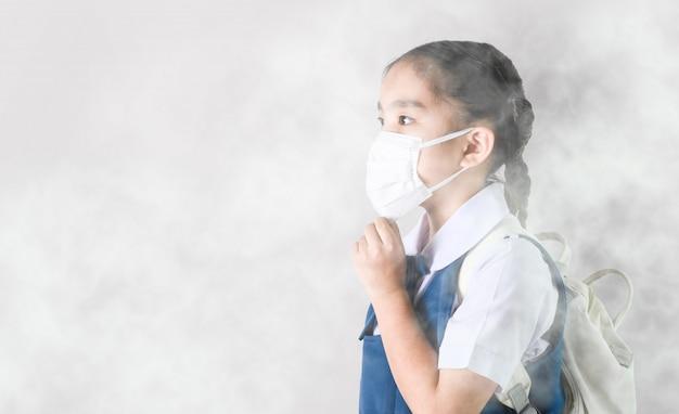 Aziatisch meisje draagt masker om stof en luchtverontreiniging pm 2,5 te beschermen