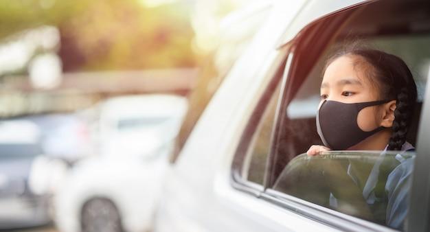 Aziatisch meisje draagt masker om stof en luchtvervuiling pm 2,5 in de auto te beschermen