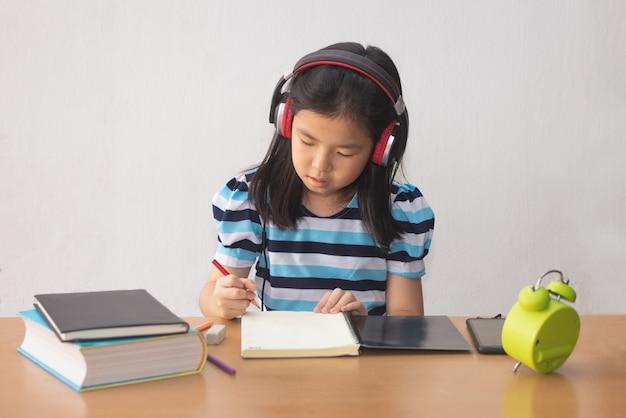 Aziatisch meisje een boek schrijven en hoofdtelefoons die aan muziek luisteren.