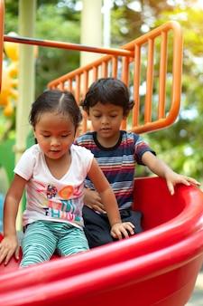 Aziatisch meisje en aziatische jongen is genieten op een speeltoestel in een school.