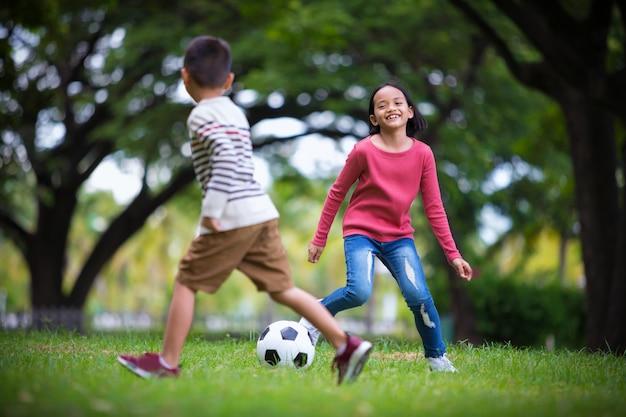 Aziatisch meisje en meisje die met voetbalspel genieten bij openlucht