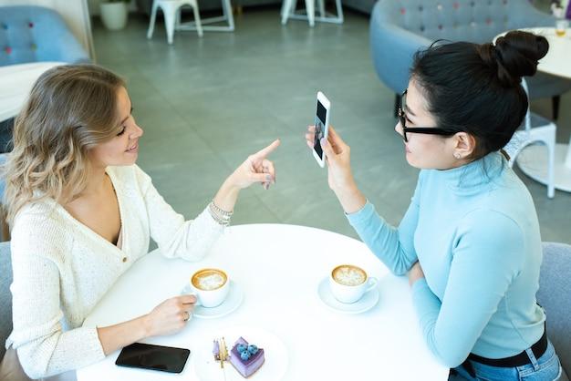 Aziatisch meisje foto's in smartphone tonen aan haar vriend wijzend op display tijdens discussie door kopje koffie in café
