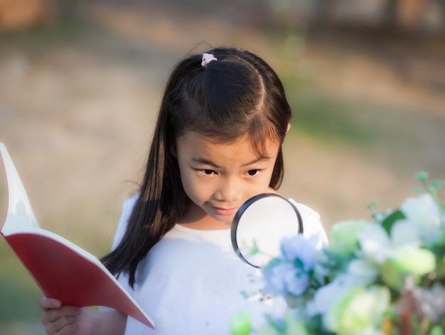Aziatisch meisje gebruikt vergrootglas in openluchtpark